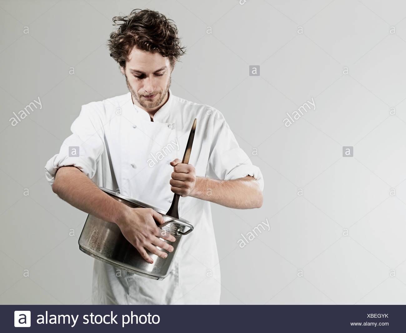 Chef stirring in pan against white background - Stock Image