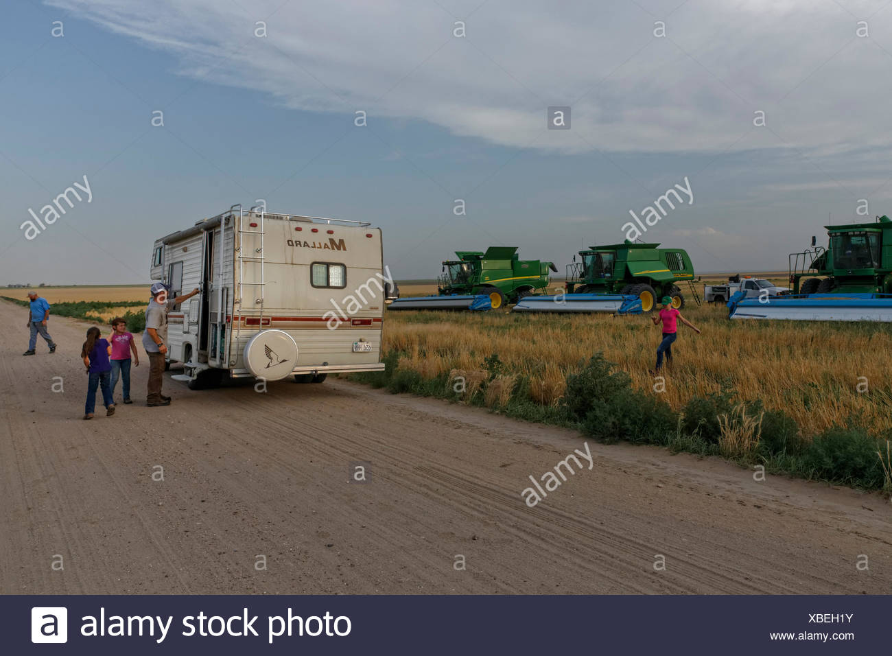 A family parks an RV in the field during the harvest so they can escape the elements and the bugs while they eat. - Stock Image