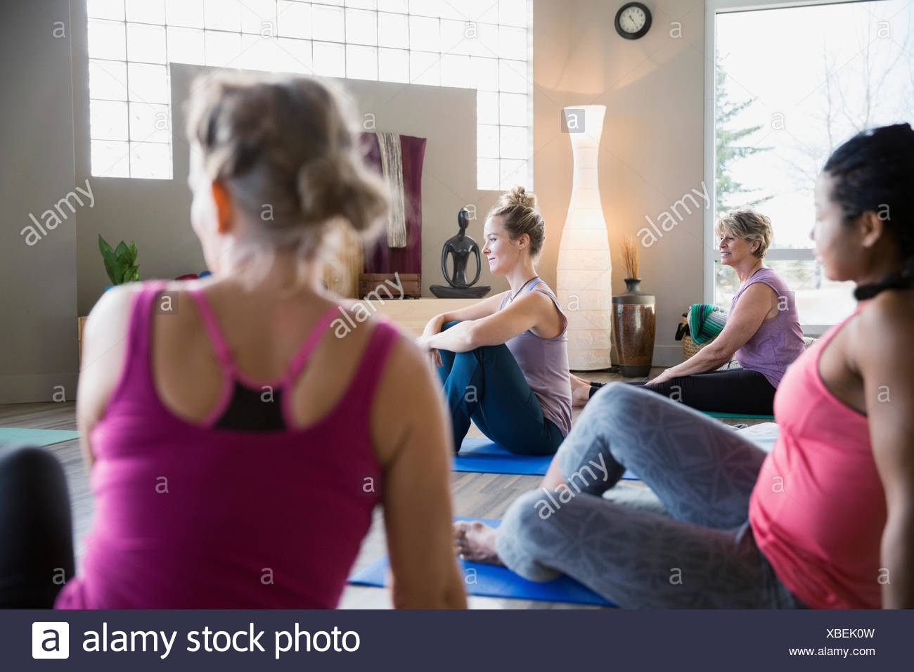 Women sitting on mats in yoga class - Stock Image