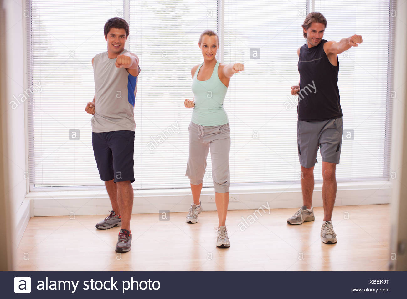 Portrait of smiling people in yoga class - Stock Image