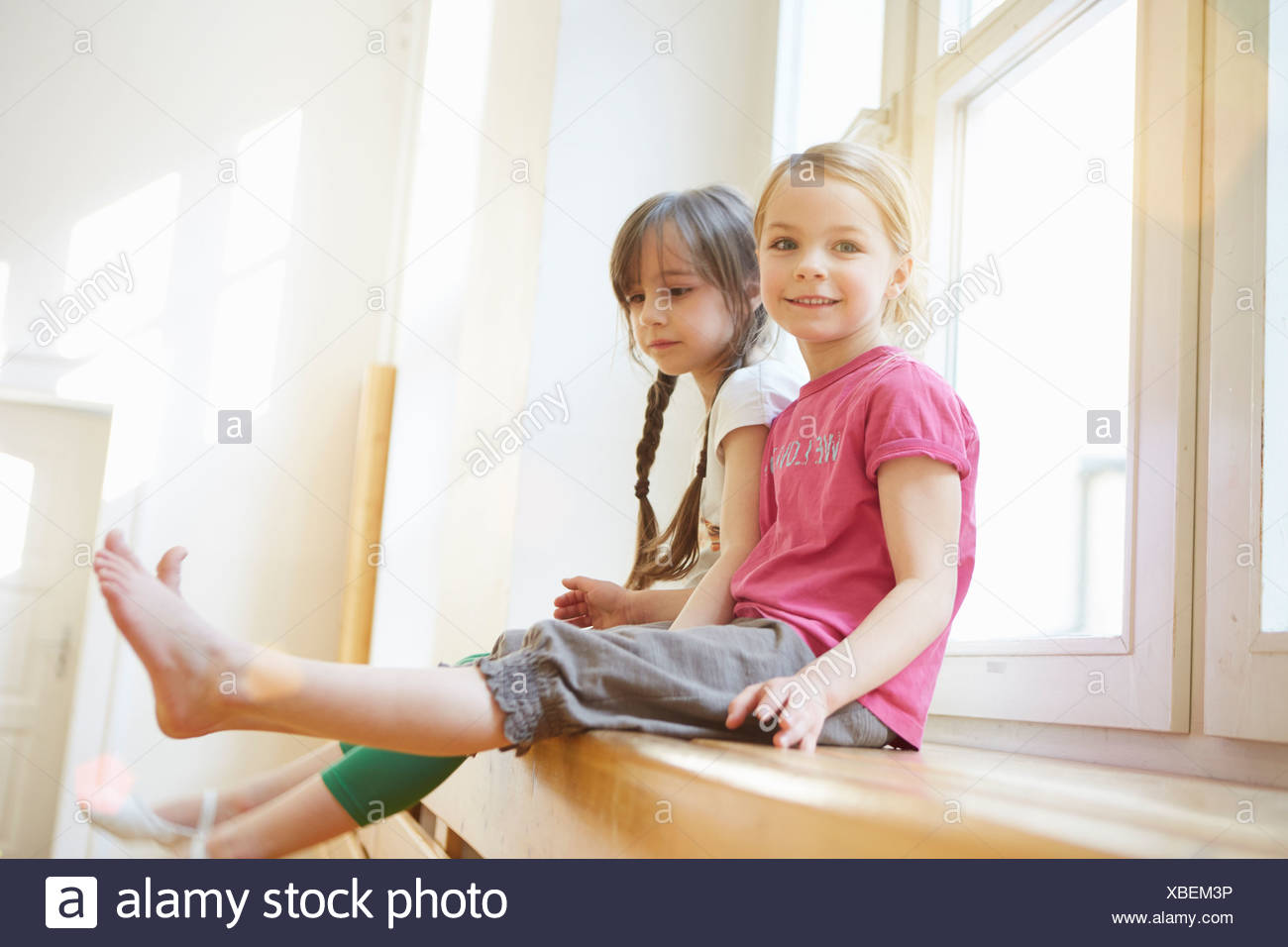 Girls sitting on apparatus in school hall - Stock Image