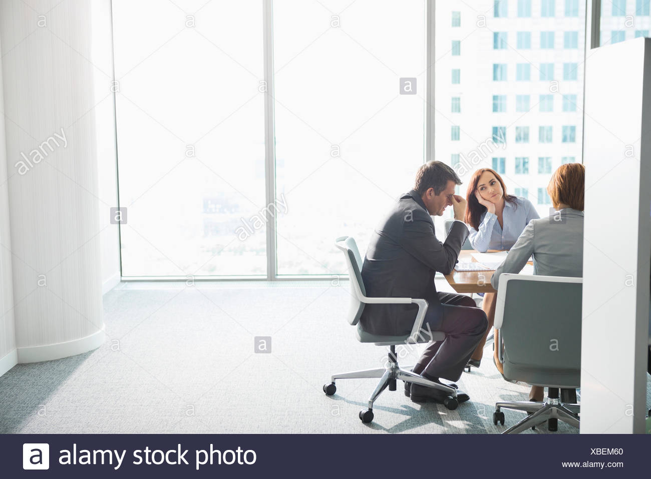 Exhausted businesspeople in meeting - Stock Image