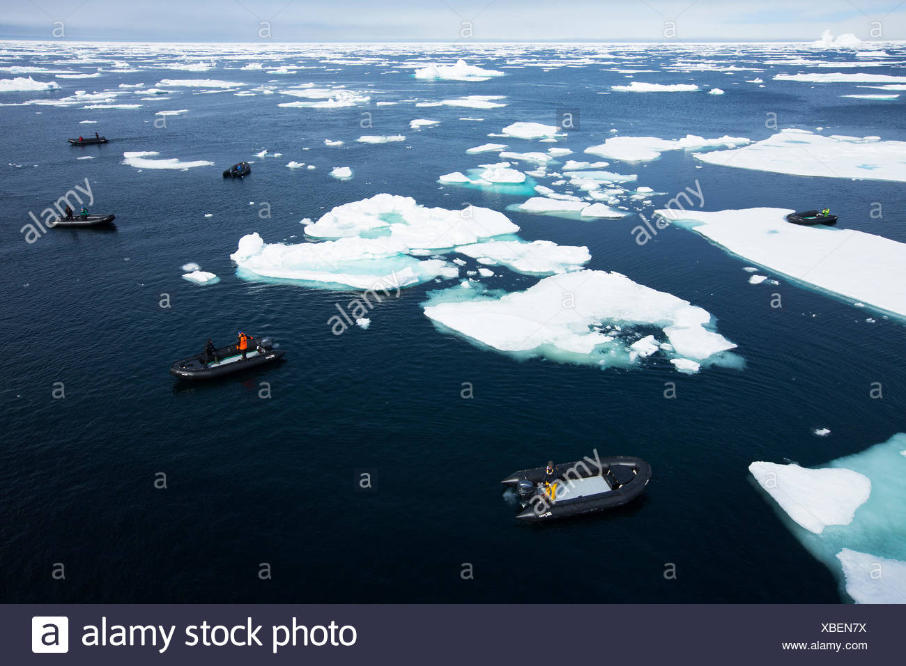 A tourist cruise ship near an ice berg off the coast of Baffin Island, Nunavut, in the Canadian arctic. - Stock Image