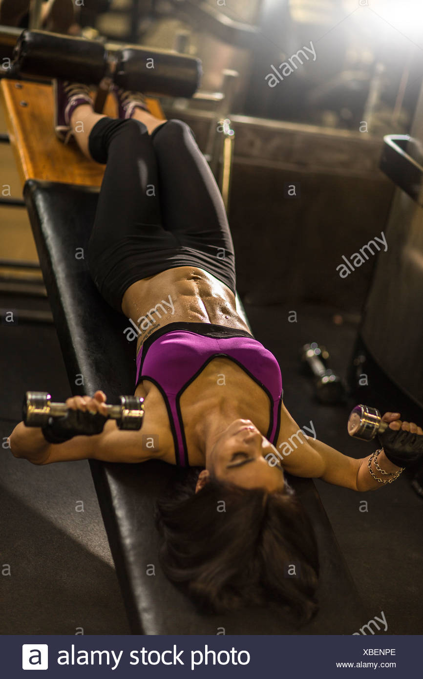 Mid adult woman doing abdominal exercise on weight bench - Stock Image