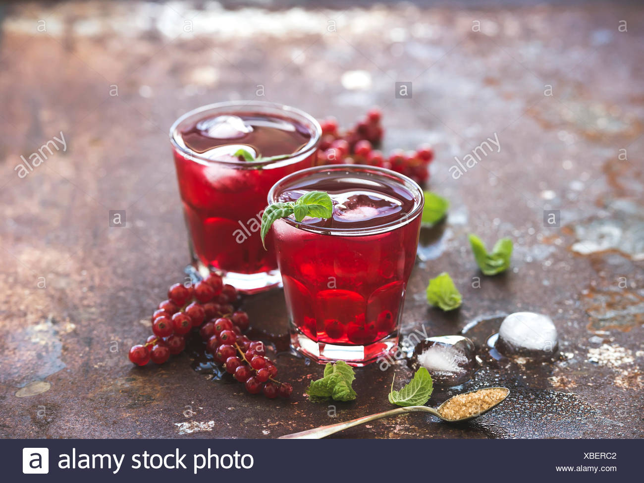 Red berry lemonade with ice and mint on grunge vintage rusty metal backdround, selective focus - Stock Image