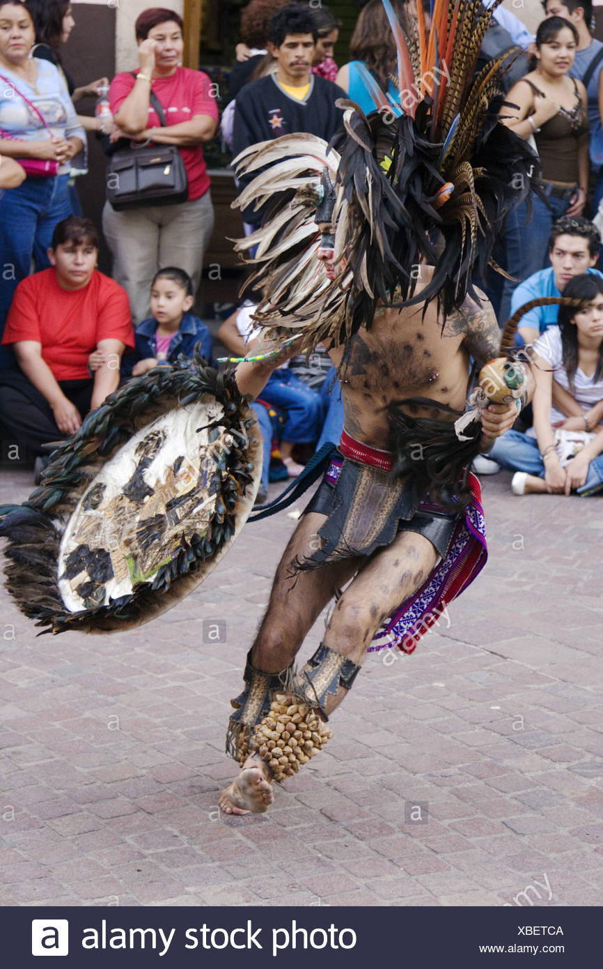 An AZTEC DANCER dressed as a WARRIOR with headdress, rattle and shield during the CERVANTINO FESTIVAL, Mexico, Guanajuato Stock Photo