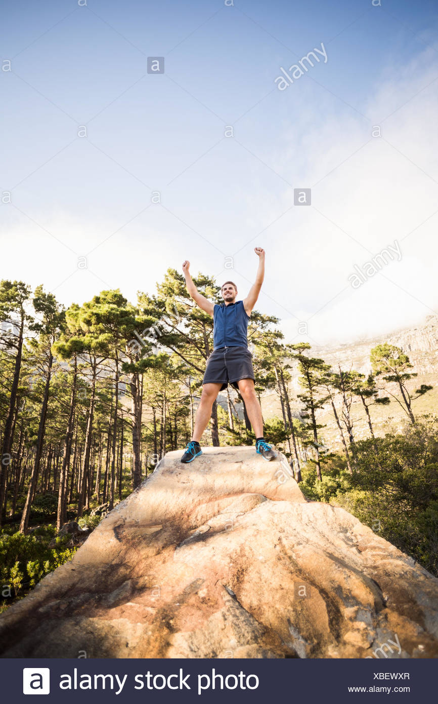 Young happy jogger standing on rock and cheering - Stock Image
