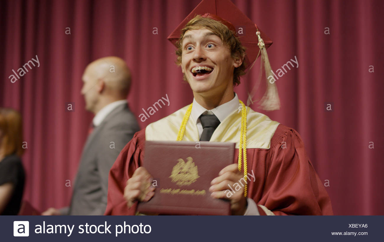 Blurred view of cheering student holding diploma on stage during graduation ceremony - Stock Image