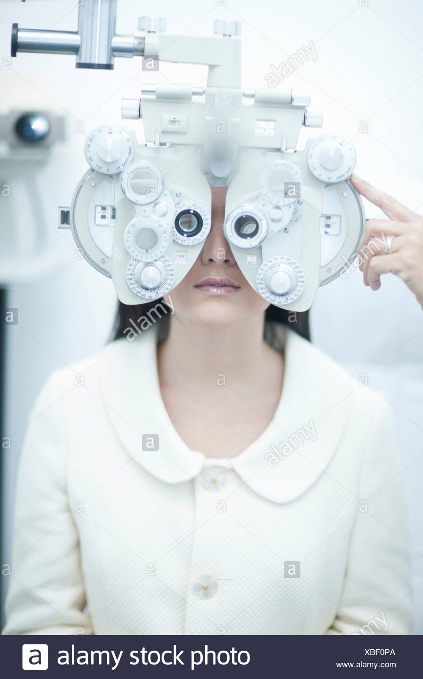 Young woman having eye test at opticians - Stock Image