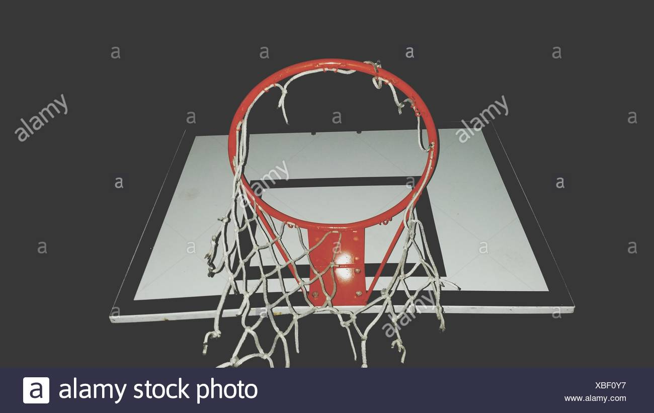 Low Angle View Of Basketball Hoop At Night - Stock Image