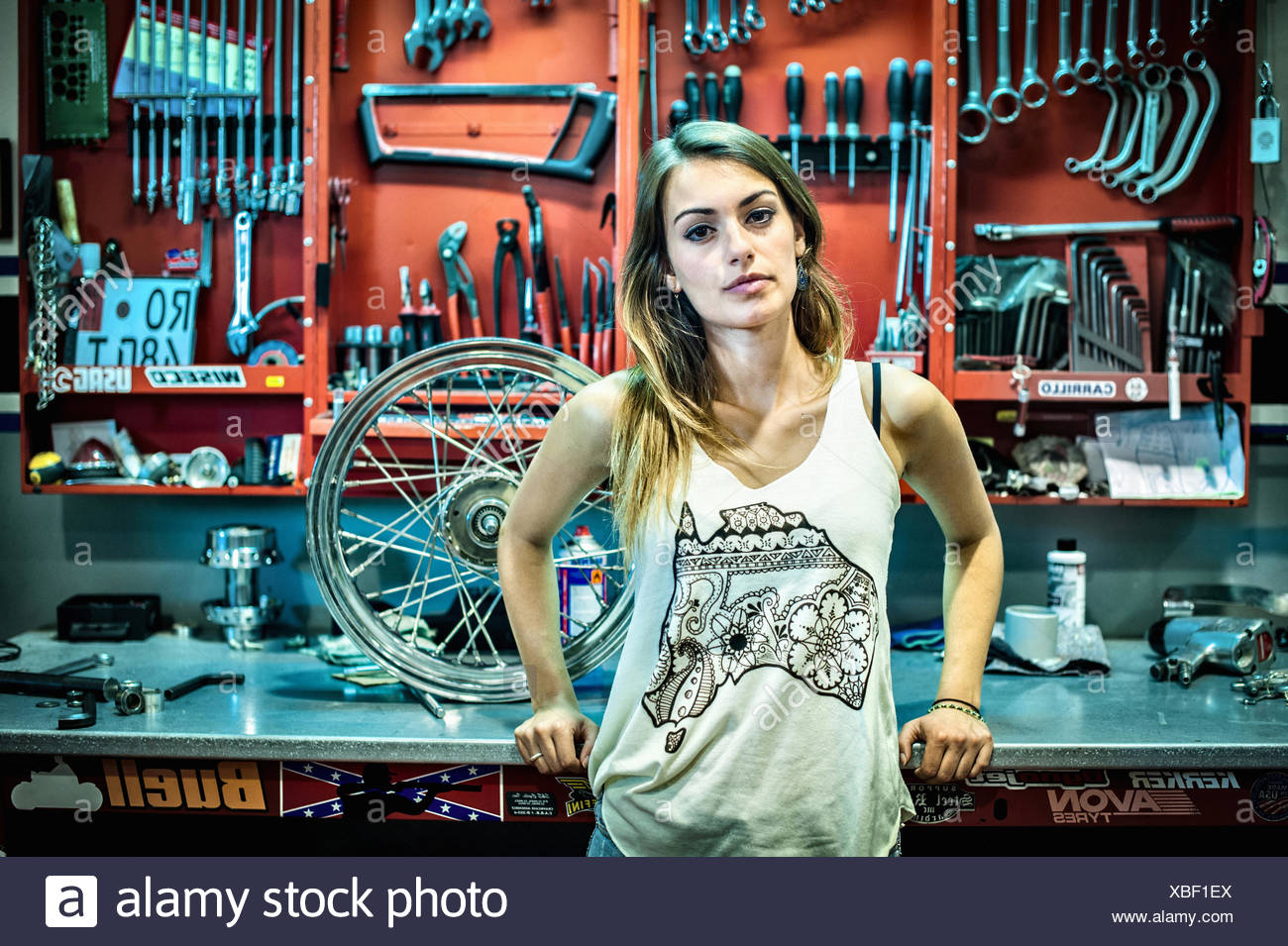 Portrait of young female mechanic in motorcycle workshop - Stock Image
