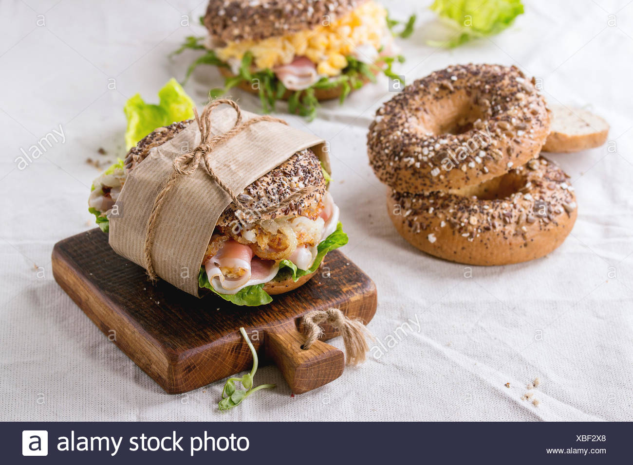 Empty and staff sprinkle seeds Whole Grain bagels with scrambled eggs, pea sprout, fried onions and prosciutto ham, making on wh - Stock Image