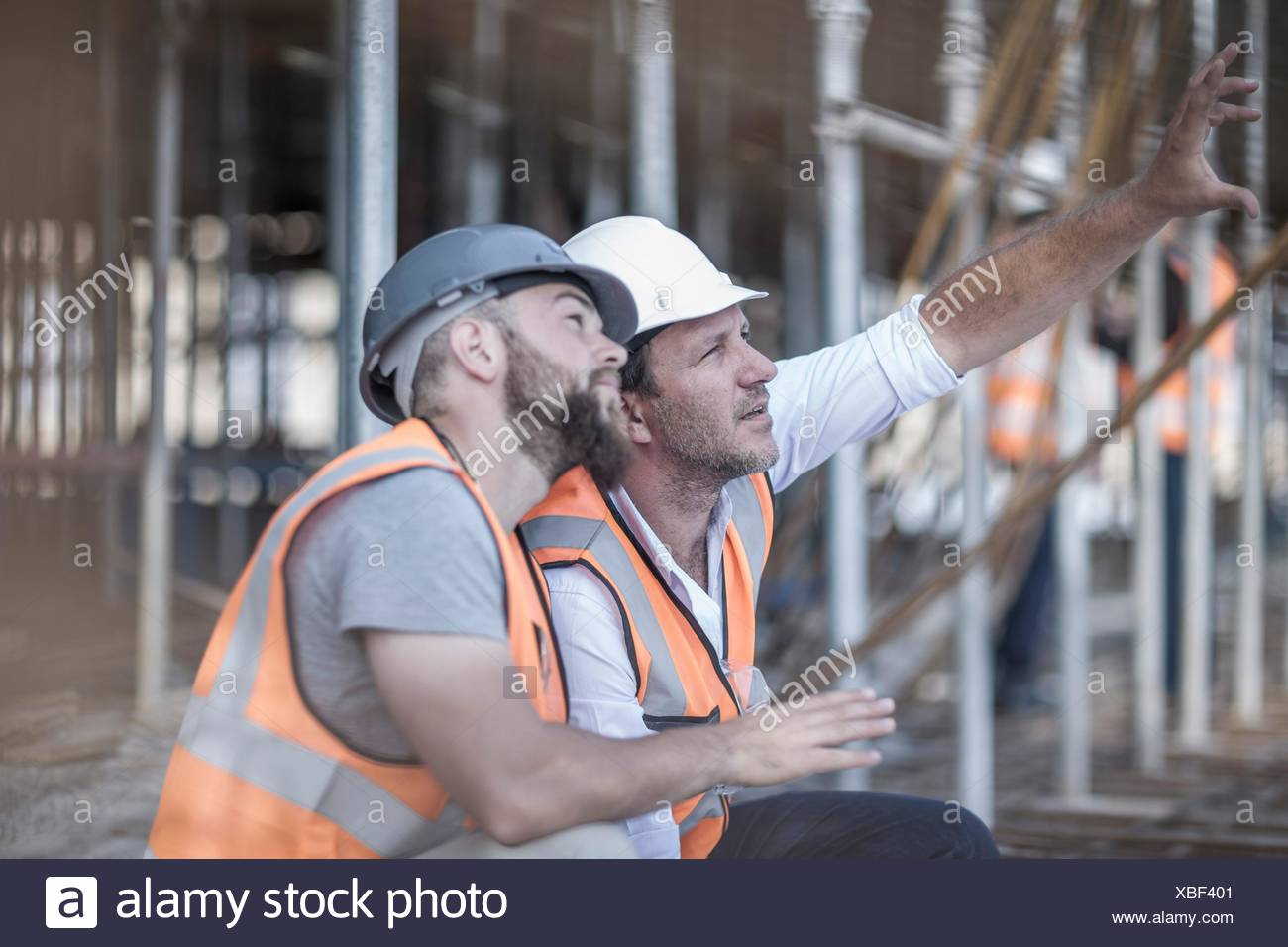 Site manager and builder looking up at steel rods on  construction site - Stock Image