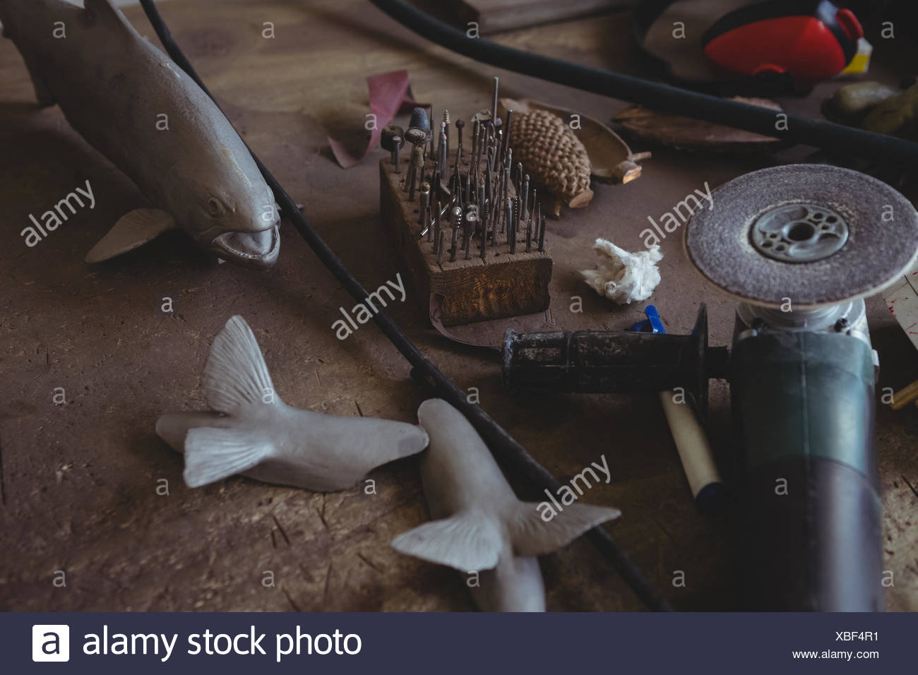 Metal fish and hand tool on worktop in workshop - Stock Image