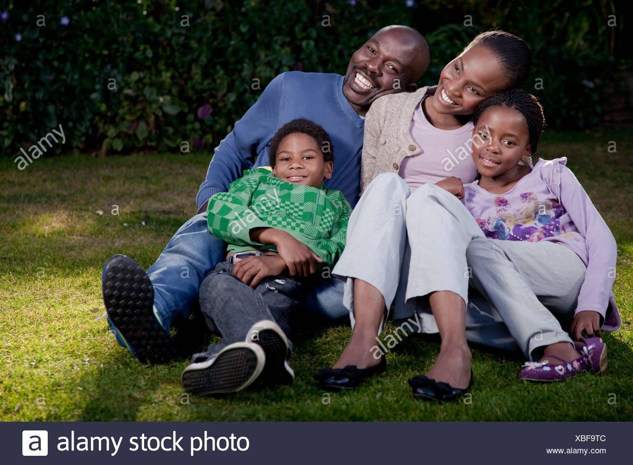 A family sitting together outside, Illovo Family, Johannesburg, South Africa. - Stock Image