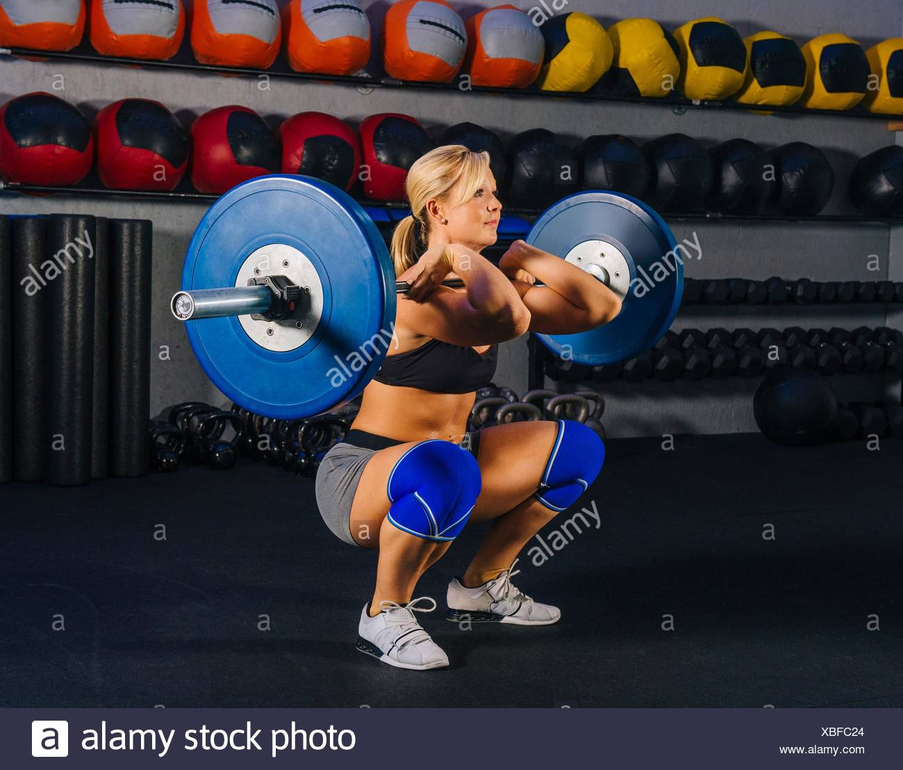 Young woman squatting with barbell in gym - Stock Image