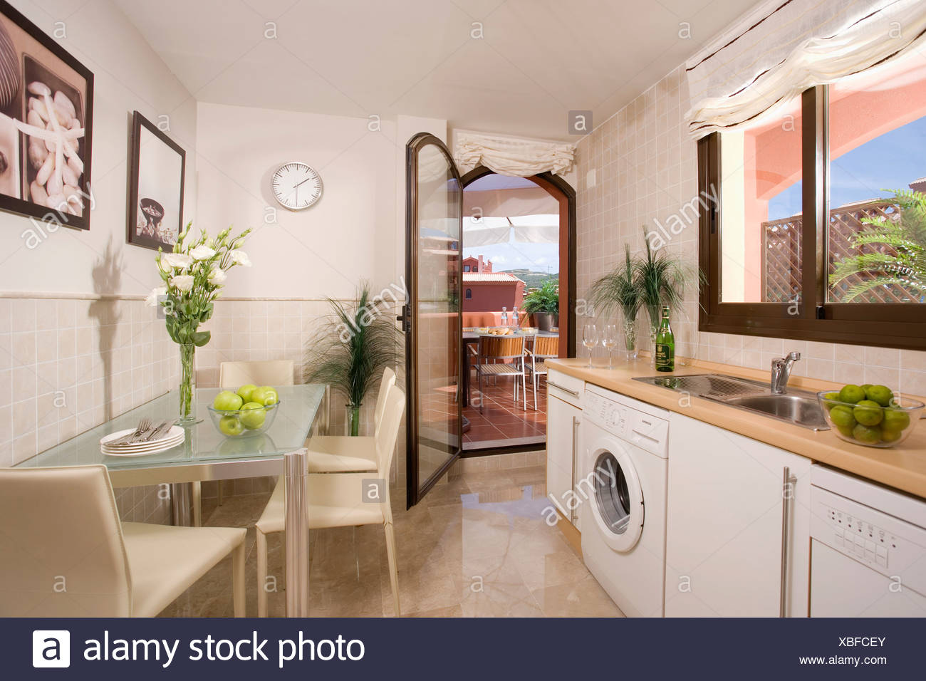 Glass Table And Beige Chirs In Small Galley Kitchen Diner In Spanish Holiday Apartment With Glass Door To Patio Stock Photo Alamy