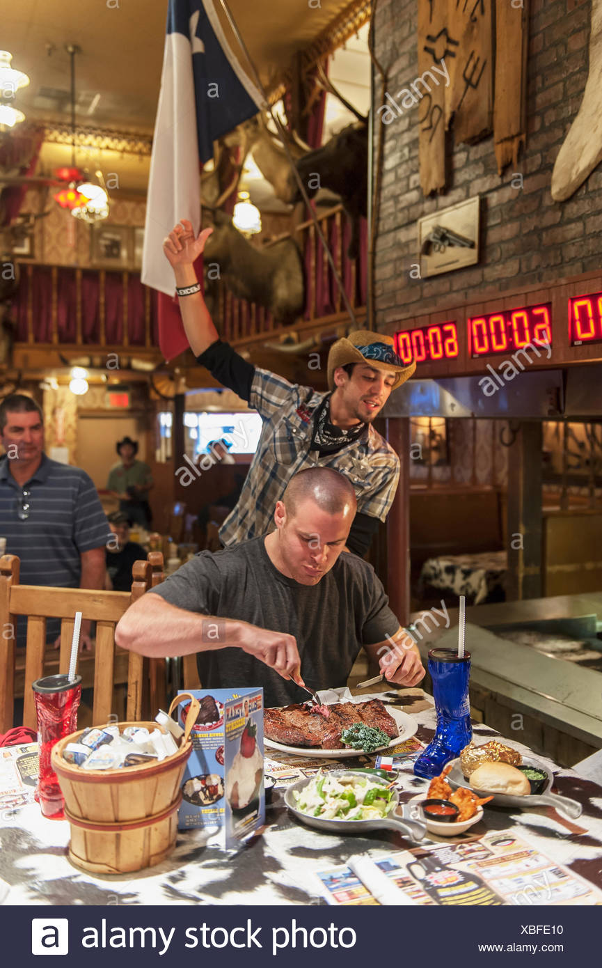 Male Contestant Begins An Attempt At The 72 Oz Steak Challenge, The Big Texan Steak Ranch Restaurant, Amarillo, Texas, Usa - Stock Image