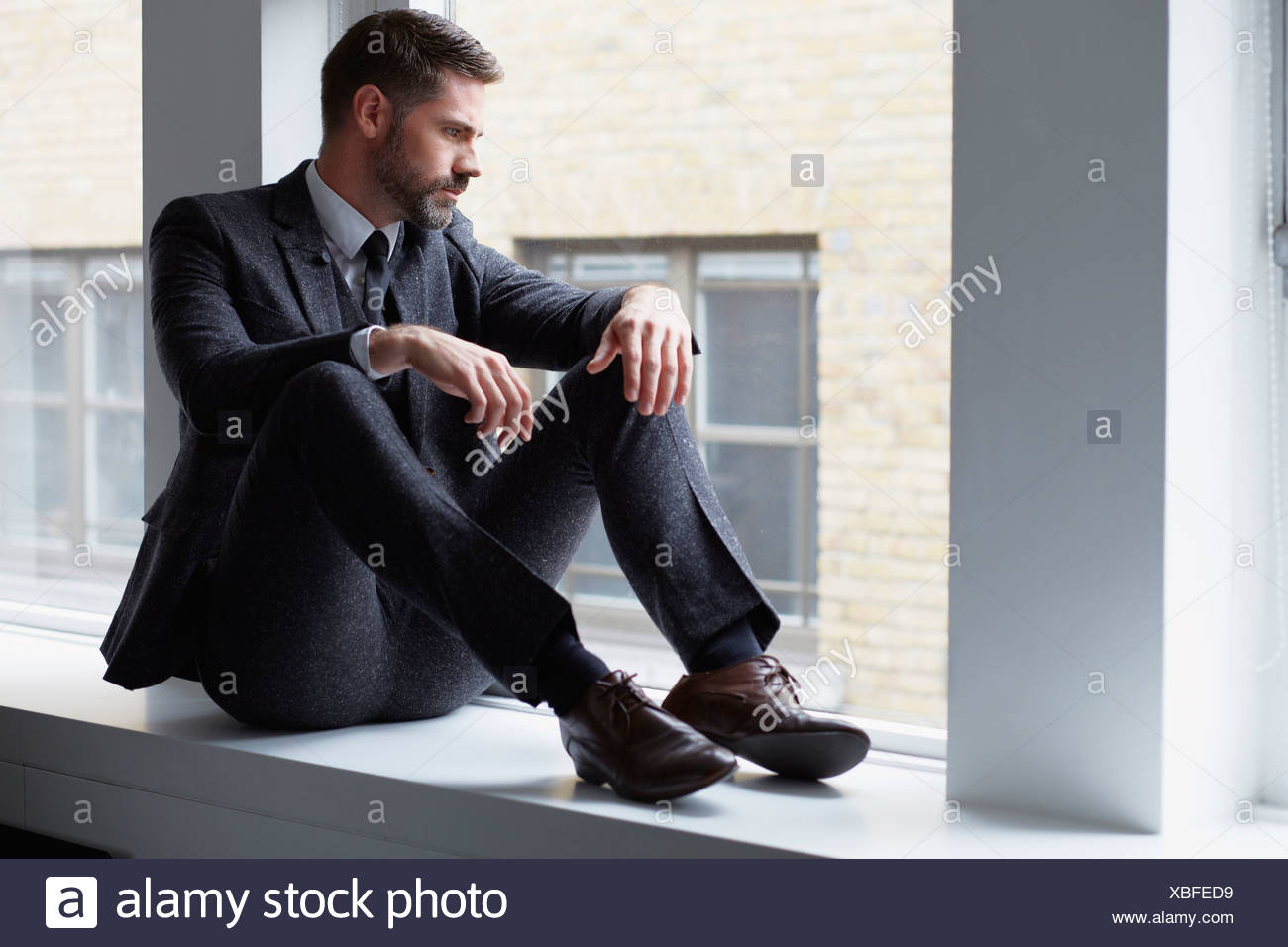 Portrait of businessman sitting on windowsill looking out of window - Stock Image
