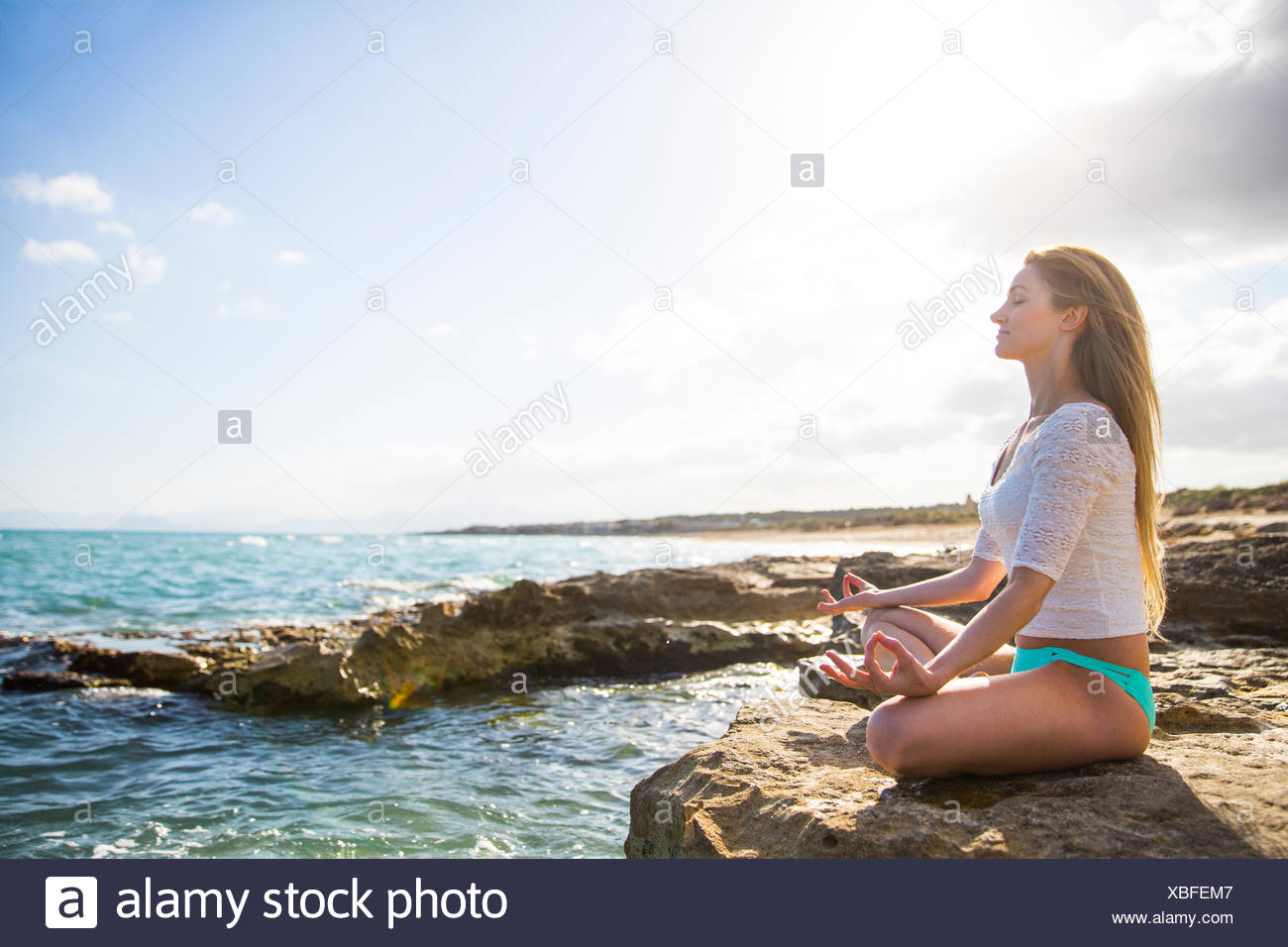 Young woman sitting on rocks by sea, in yoga position - Stock Image
