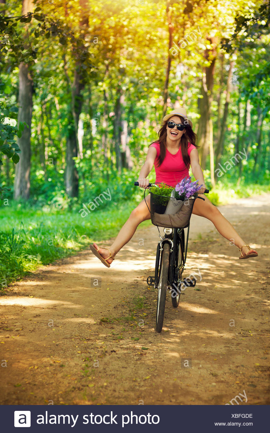 Happy woman enjoying a cycle ride in forest, Debica, Poland. - Stock Image