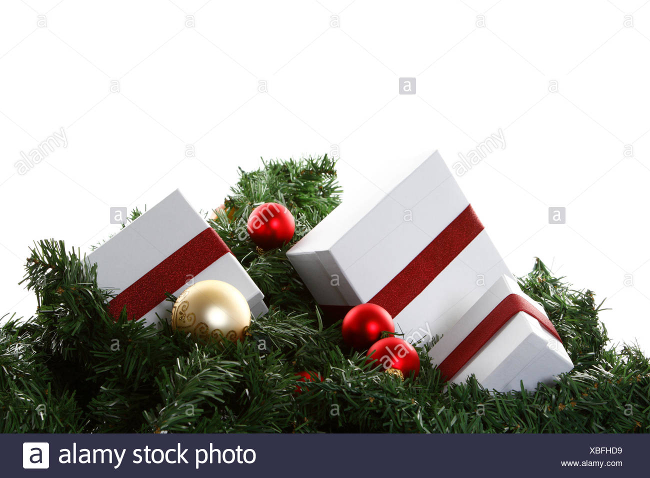 Christmas presents and baubles on artificial fir sprigs - Stock Image