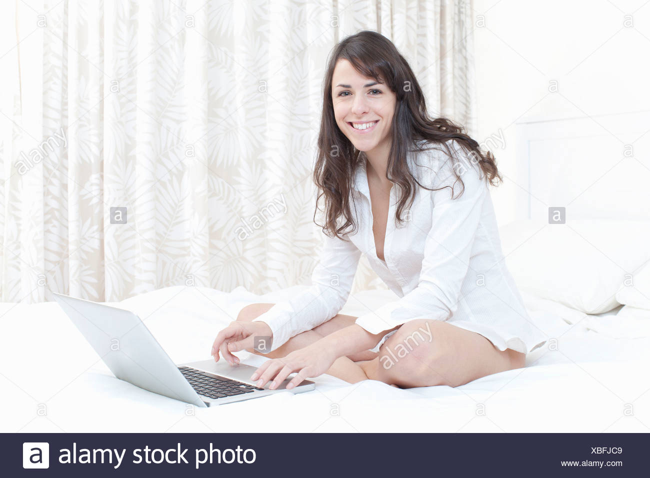 Woman using laptop on bed - Stock Image