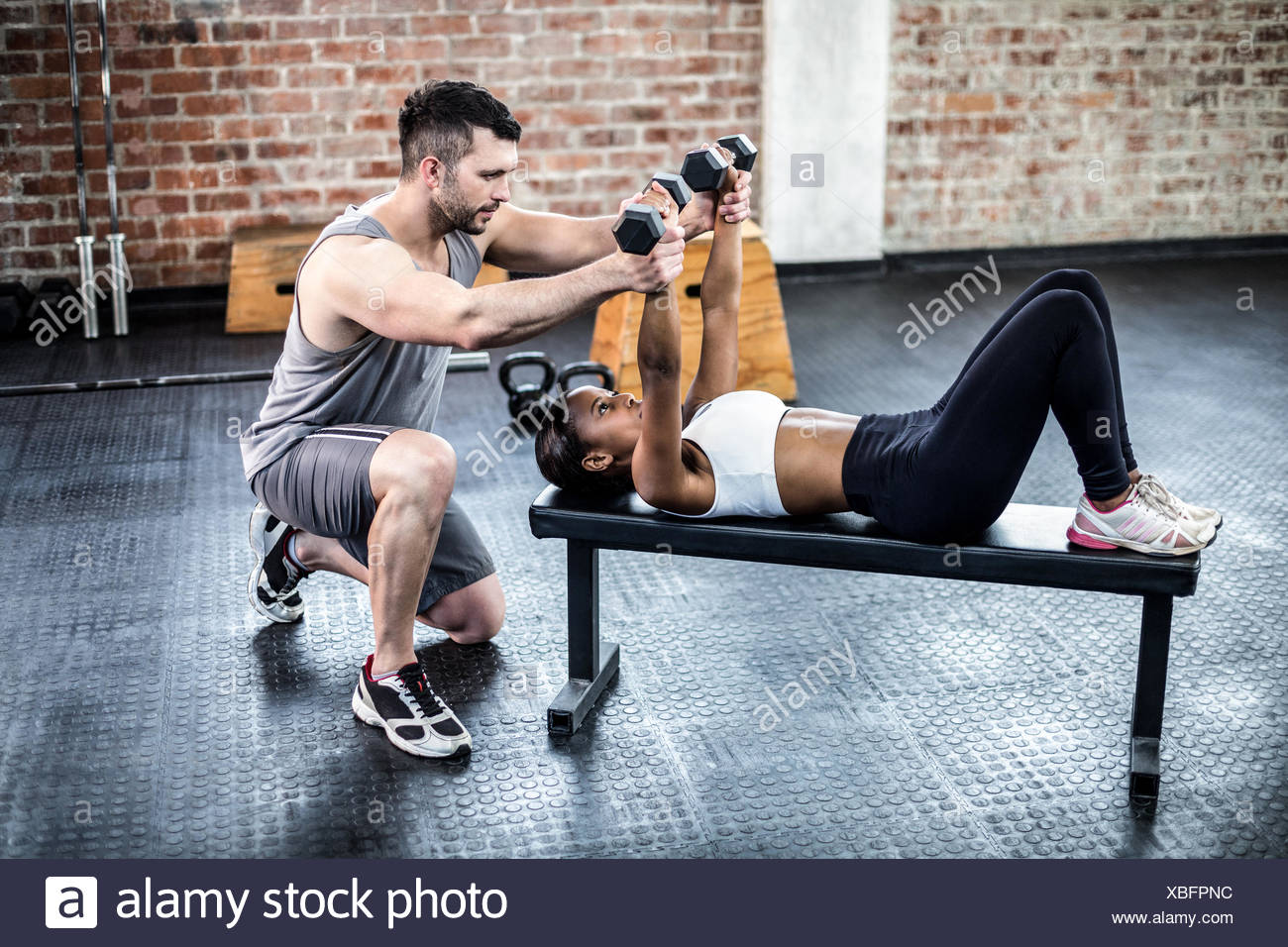 Personal trainer working with client holding dumbbell - Stock Image