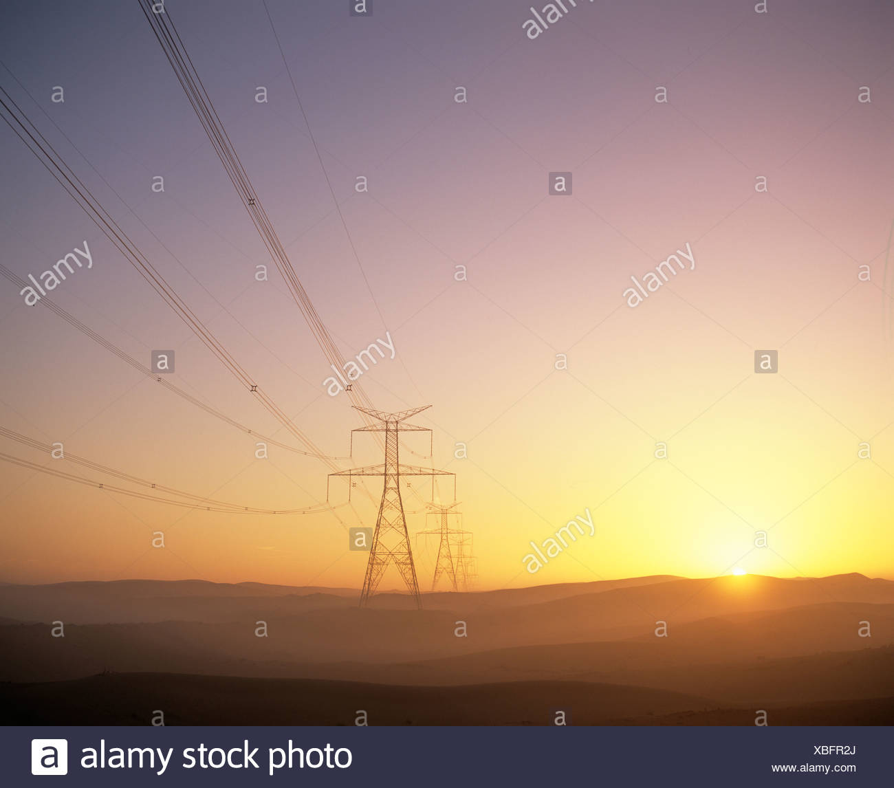 Electricity pylons at sunset in a desert.Photographed in the United Arab Emirates. - Stock Image
