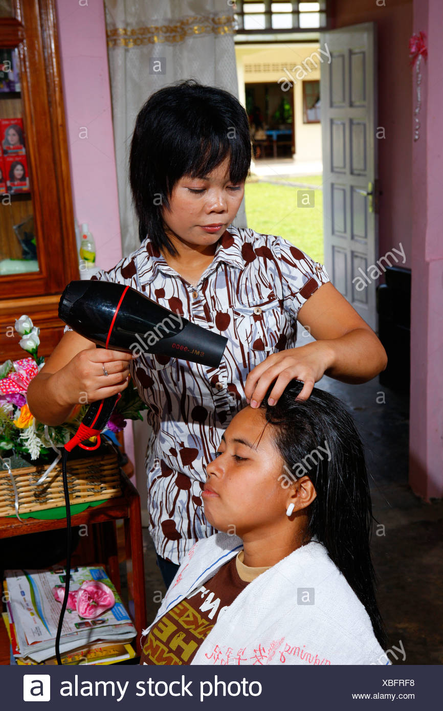 Young woman blowdrying hair during a hairdressing apprenticeship, vocational training center, Siantar, Sumatra, Indonesia, Asia - Stock Image