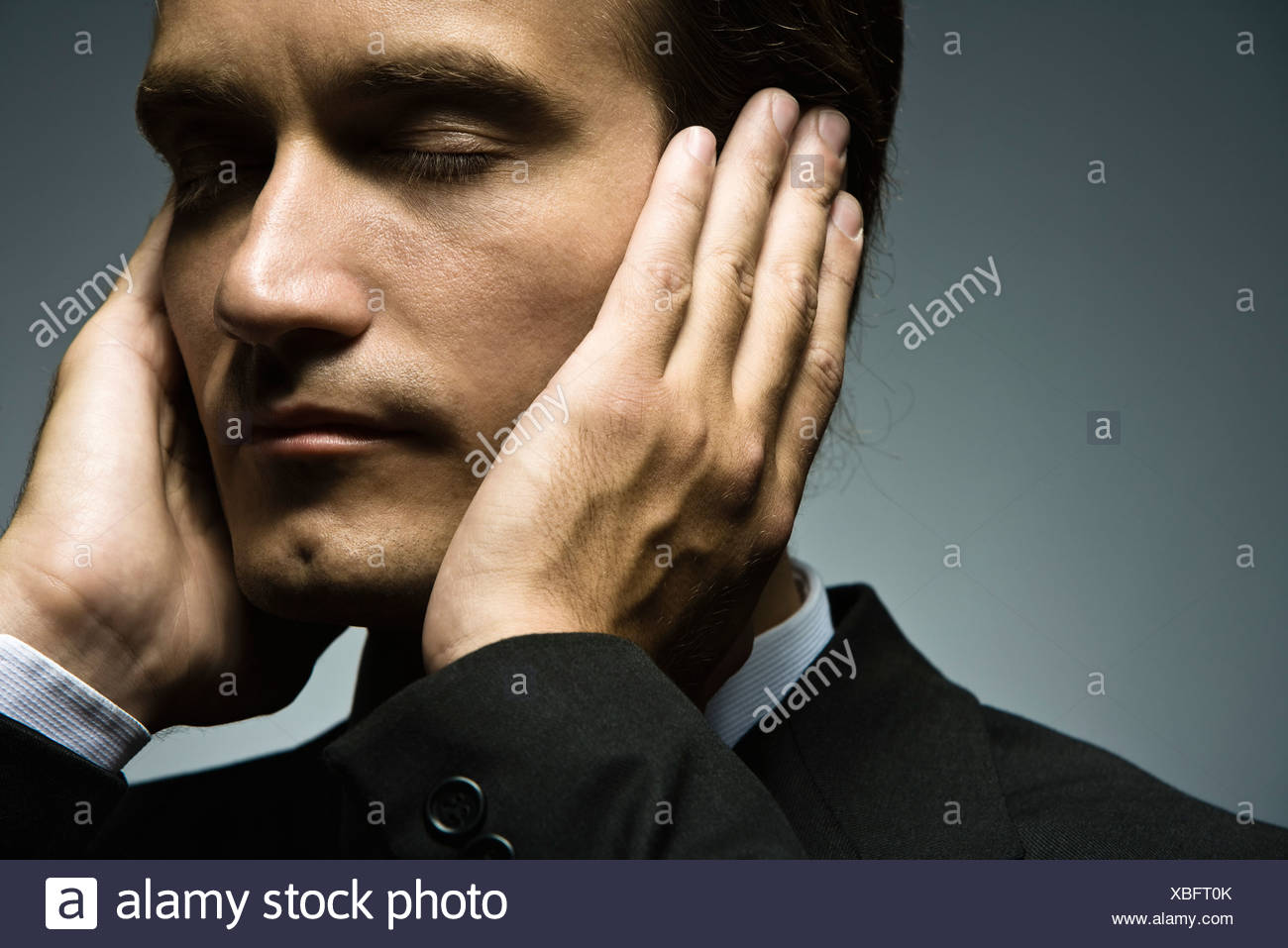Man with hands held over ears and eyes closed - Stock Image