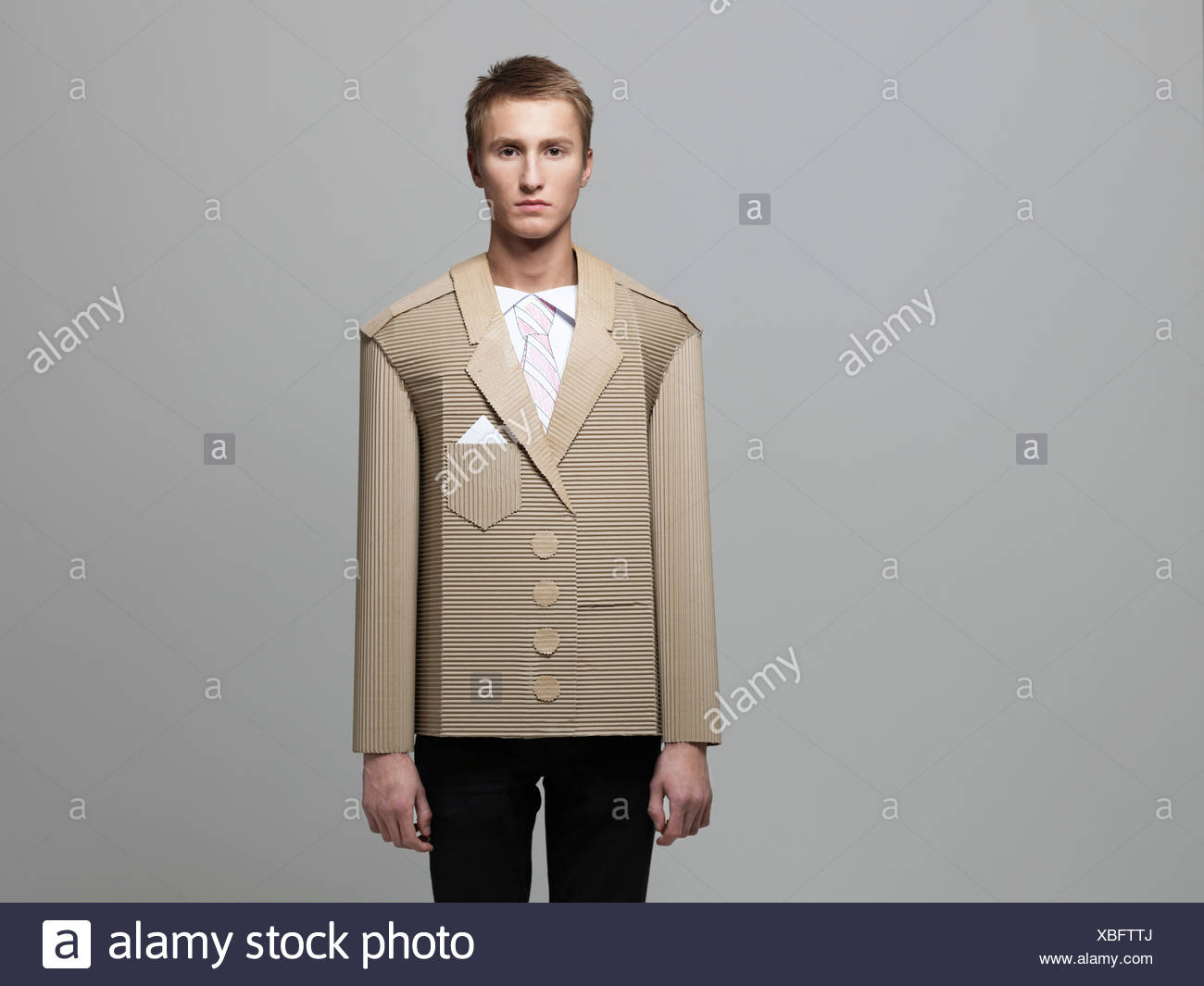 Man wearing jacket made out of corrugated cardboard - Stock Image