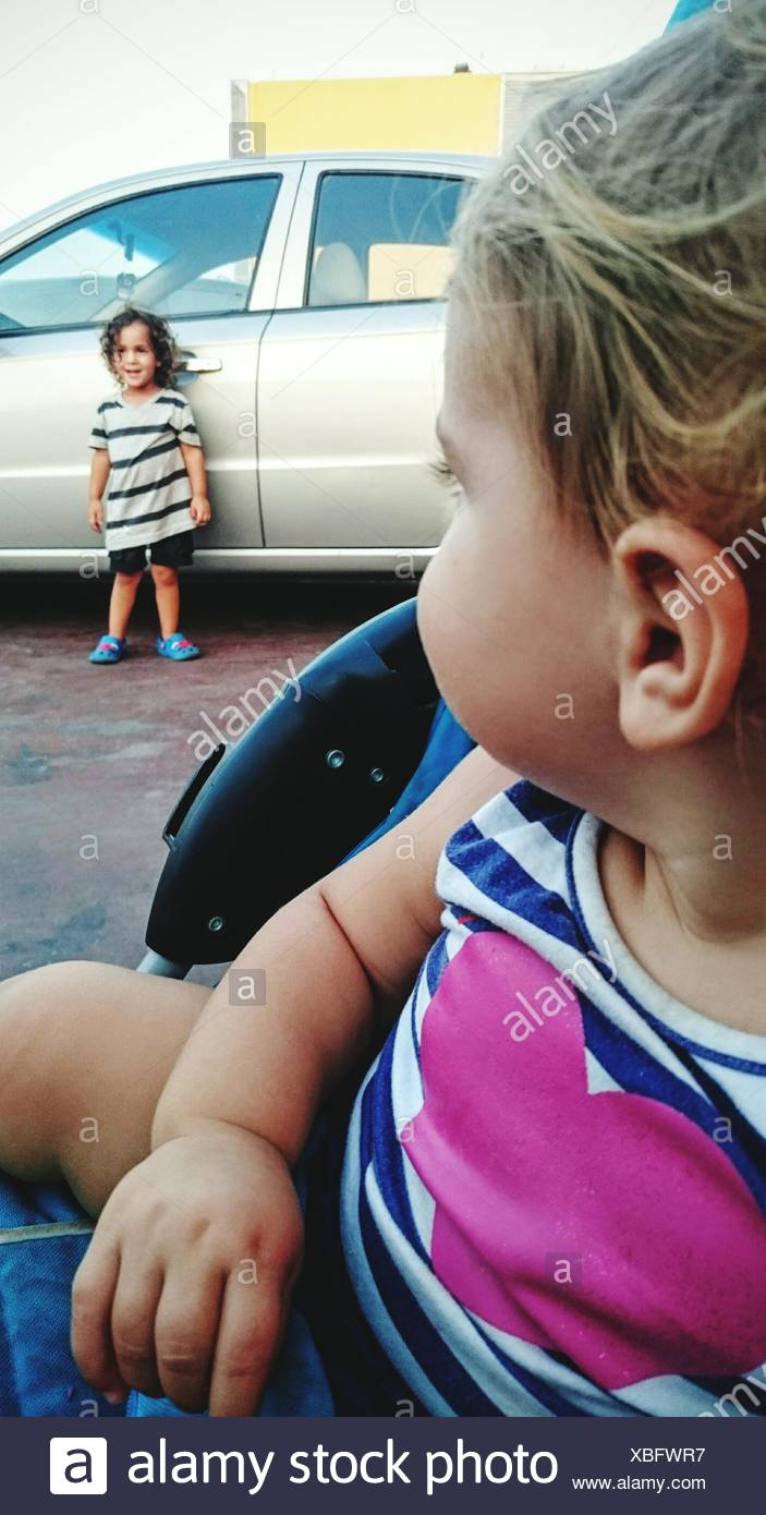 Girl Looking At Brother Standing Against Car On Road - Stock Image