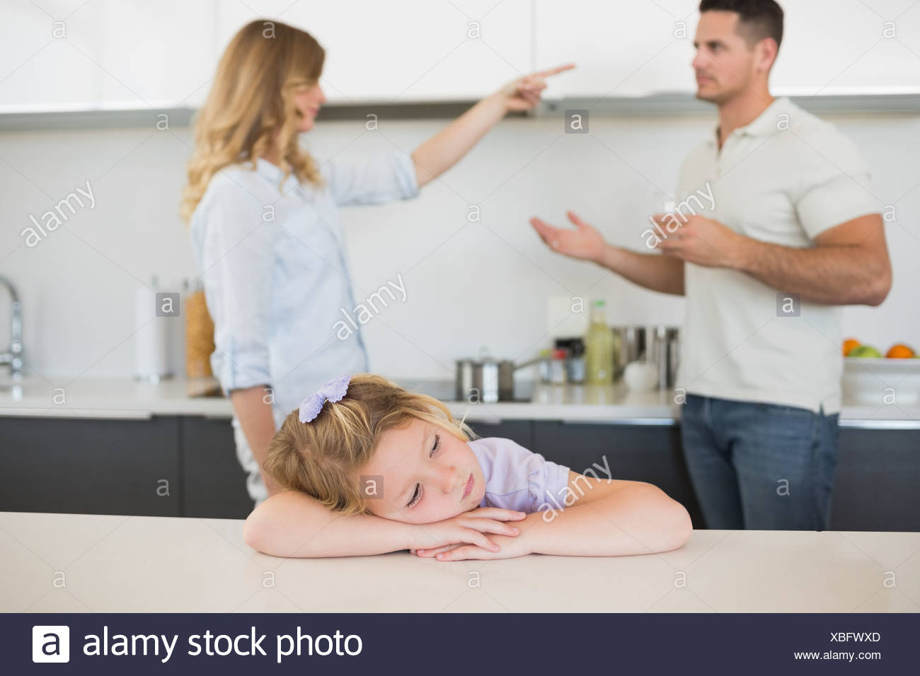 Girl at table with parents arguing in background - Stock Image