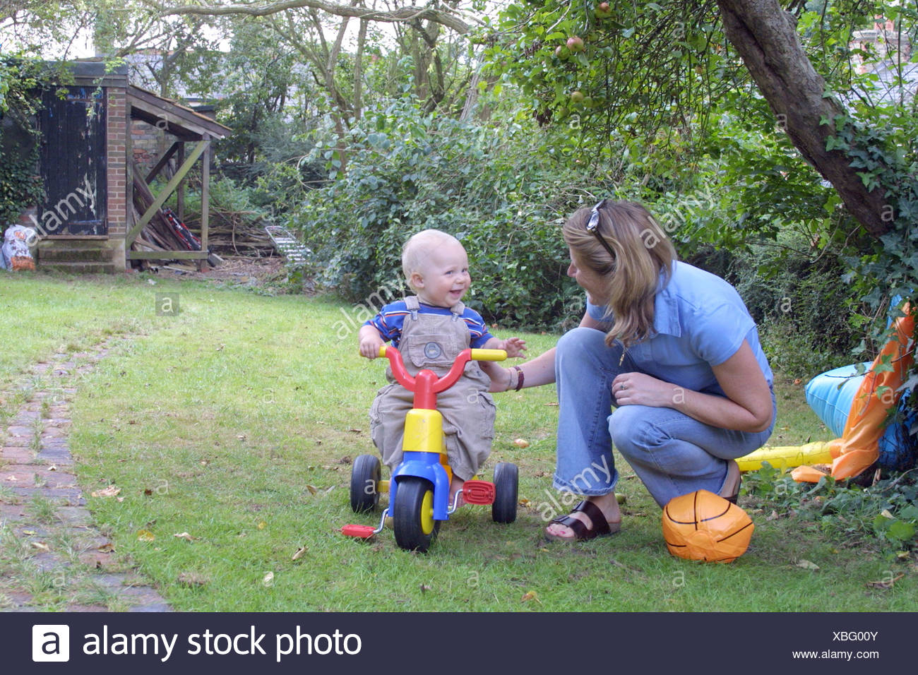 mother assisting her toddler on a tricycle - Stock Image
