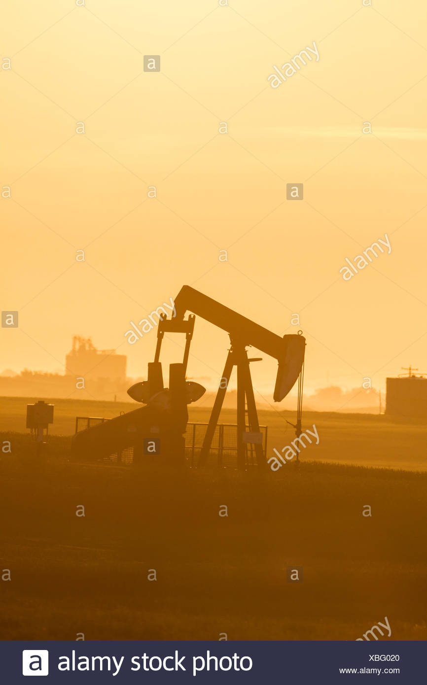 Oil pumpjack silhouetted against the rising sun in Southern Manitoba, Canada - Stock Image