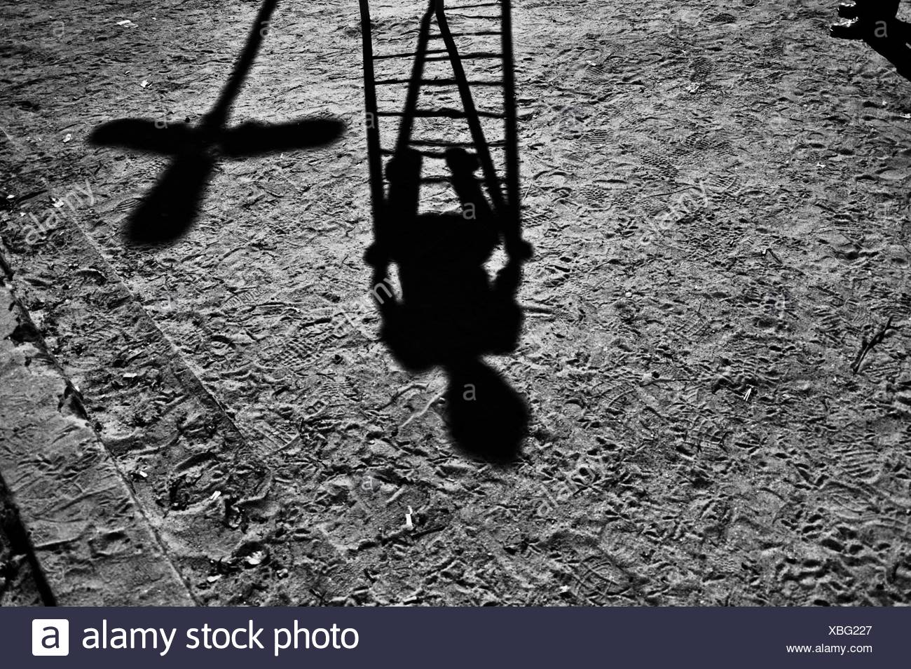 Shadow of a child playing in a playground - Stock Image