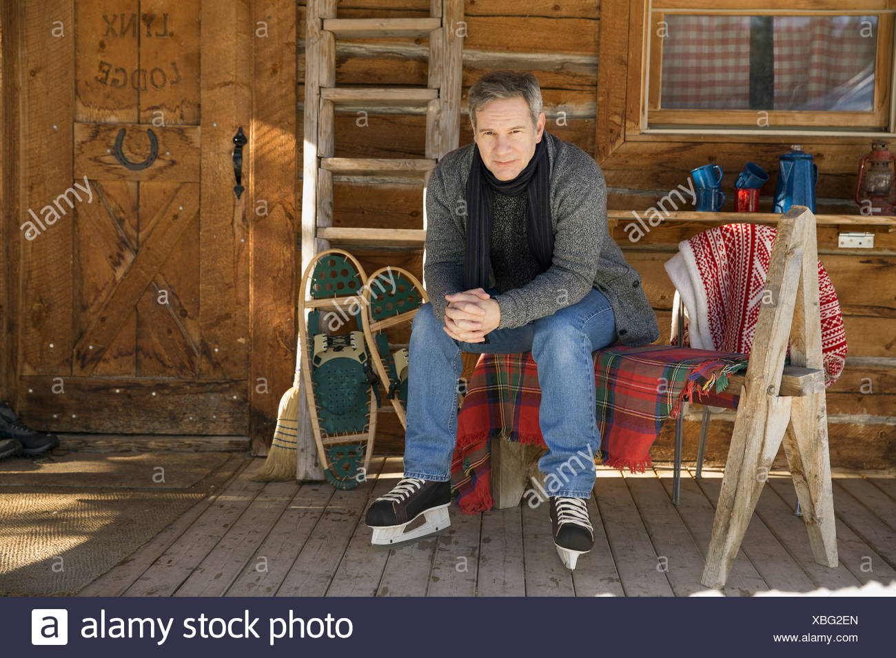 Man sitting outside of cabin wearing ice skates - Stock Image