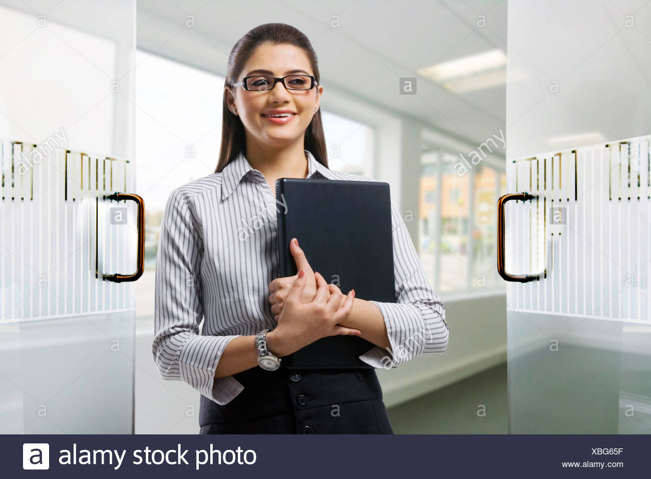 Secretary holding a laptop in the office - Stock Image