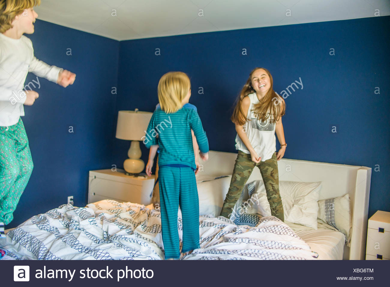 Teenage girl jumping on bed with younger brothers - Stock Image