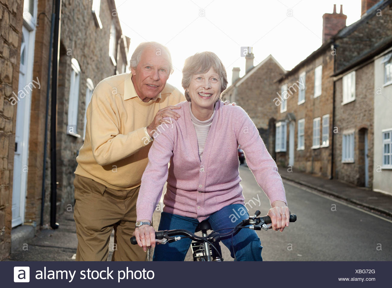 Husband supporting wife on bicycle - Stock Image