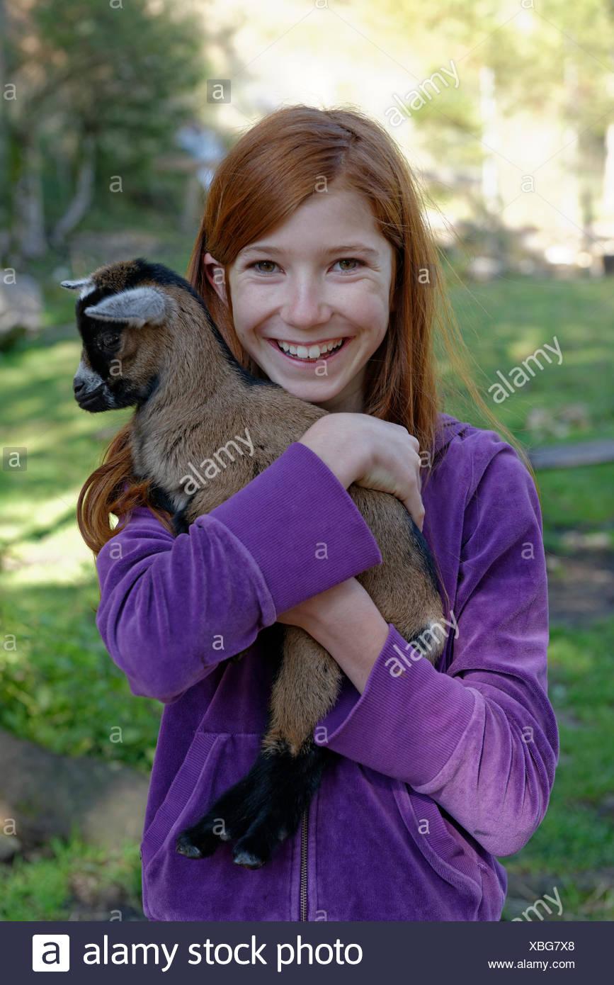Girl holding a dwarf goat in the petting zoo at Schopperalm, Schopper Alm, Gießenbachklamm gorge near Kiefersfelden, Inn Valley - Stock Image