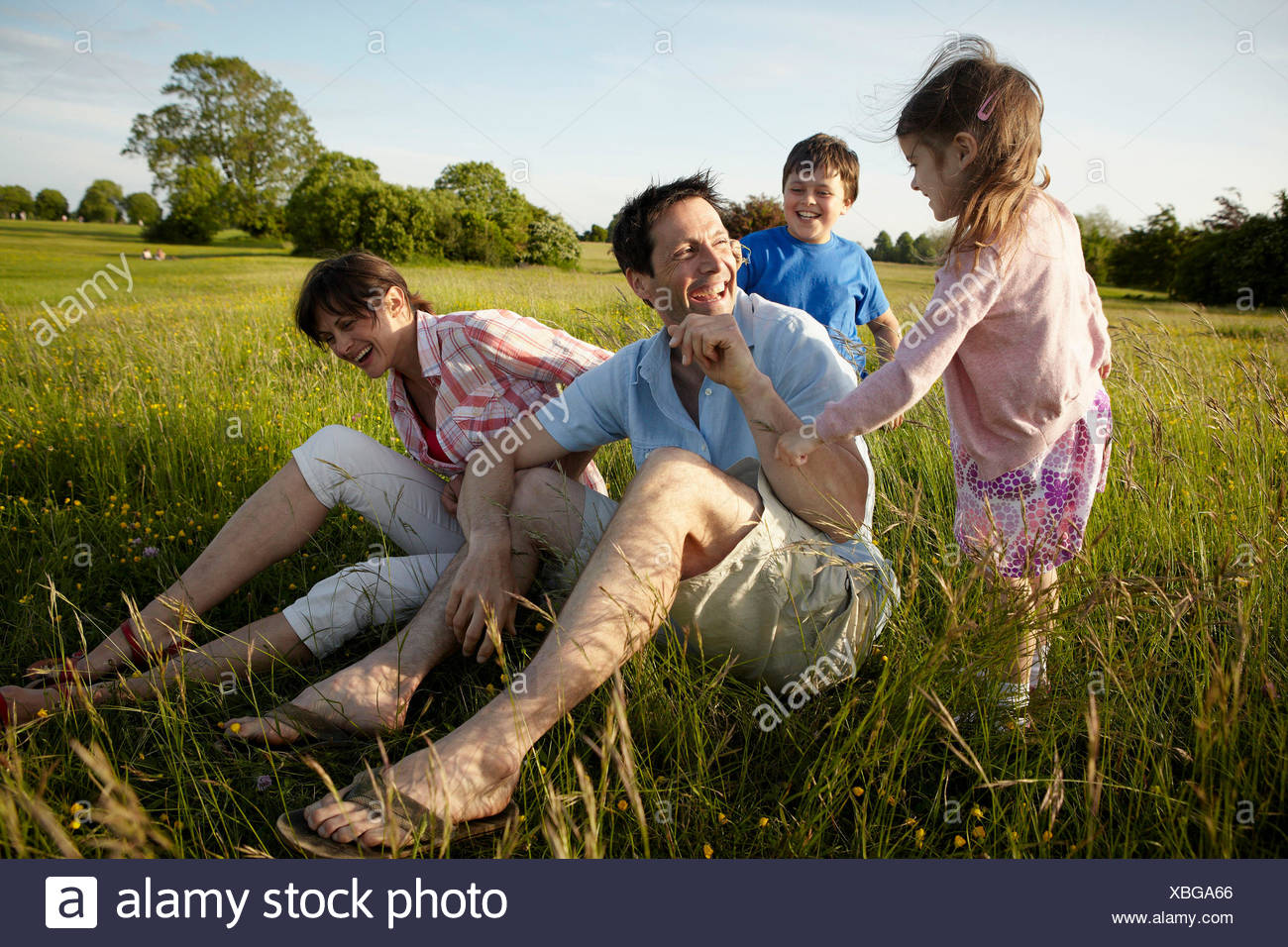 A family, two parents and two children outdoors on a summer evening. - Stock Image
