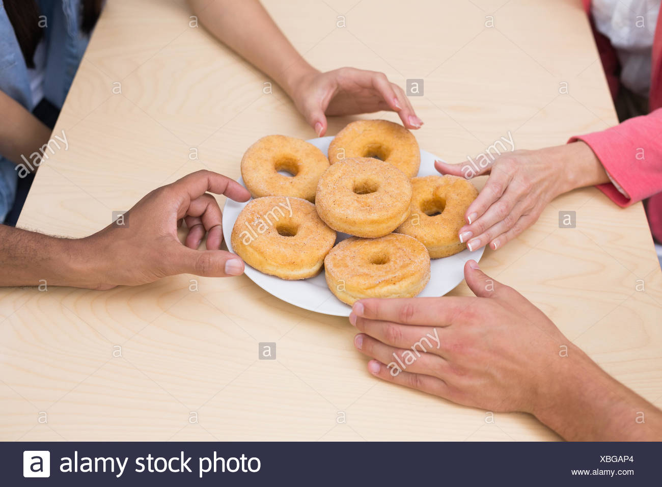 Business team reaching for doughnuts on table - Stock Image