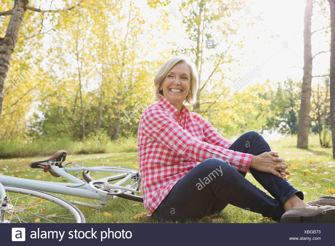 Happy woman with bicycle sitting in park - Stock Image