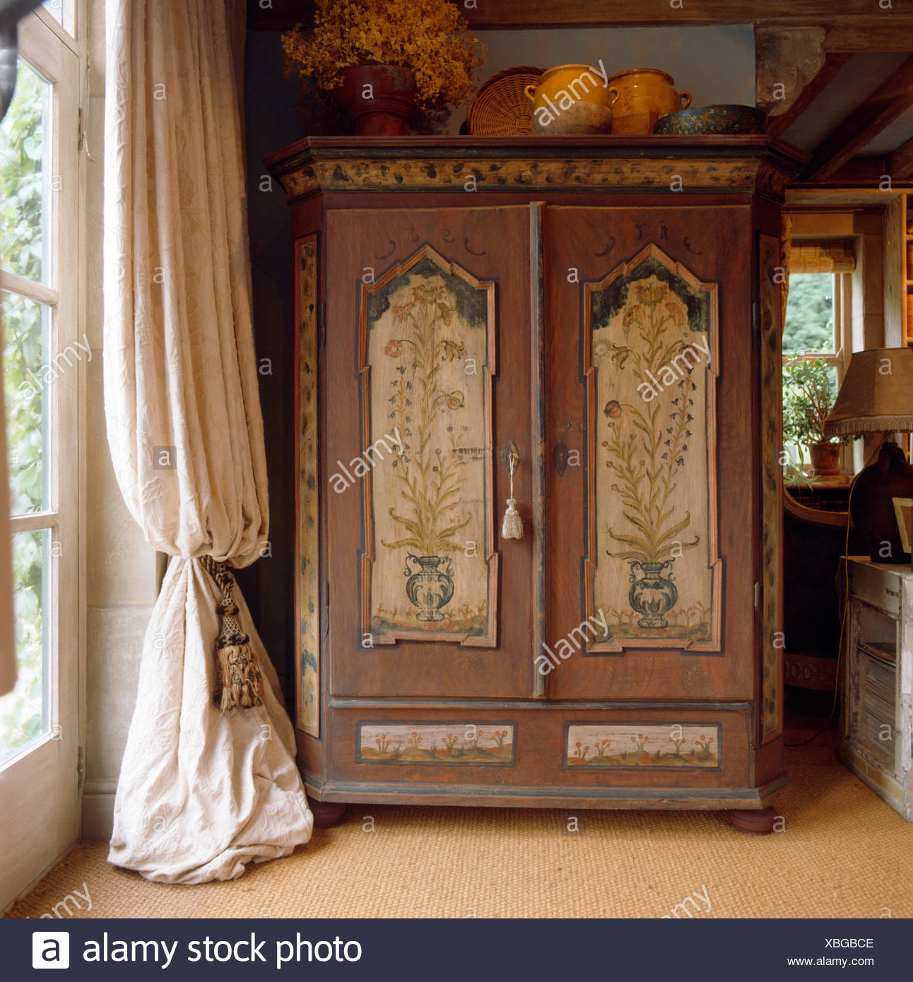 Painted antique armoire beside window with heavy cream curtain in country living room - Stock Image