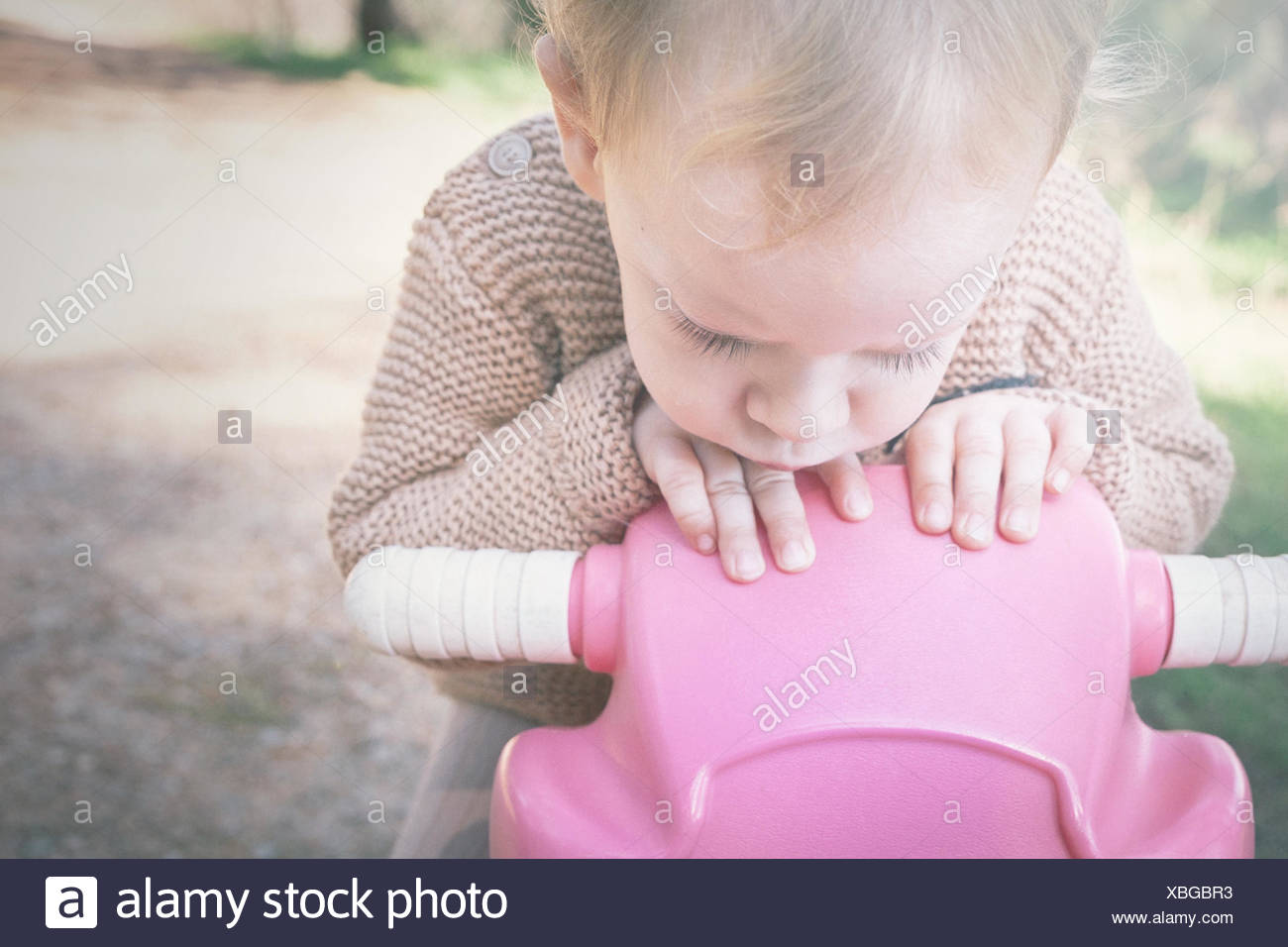 Boy sitting on a toy bicycle - Stock Image