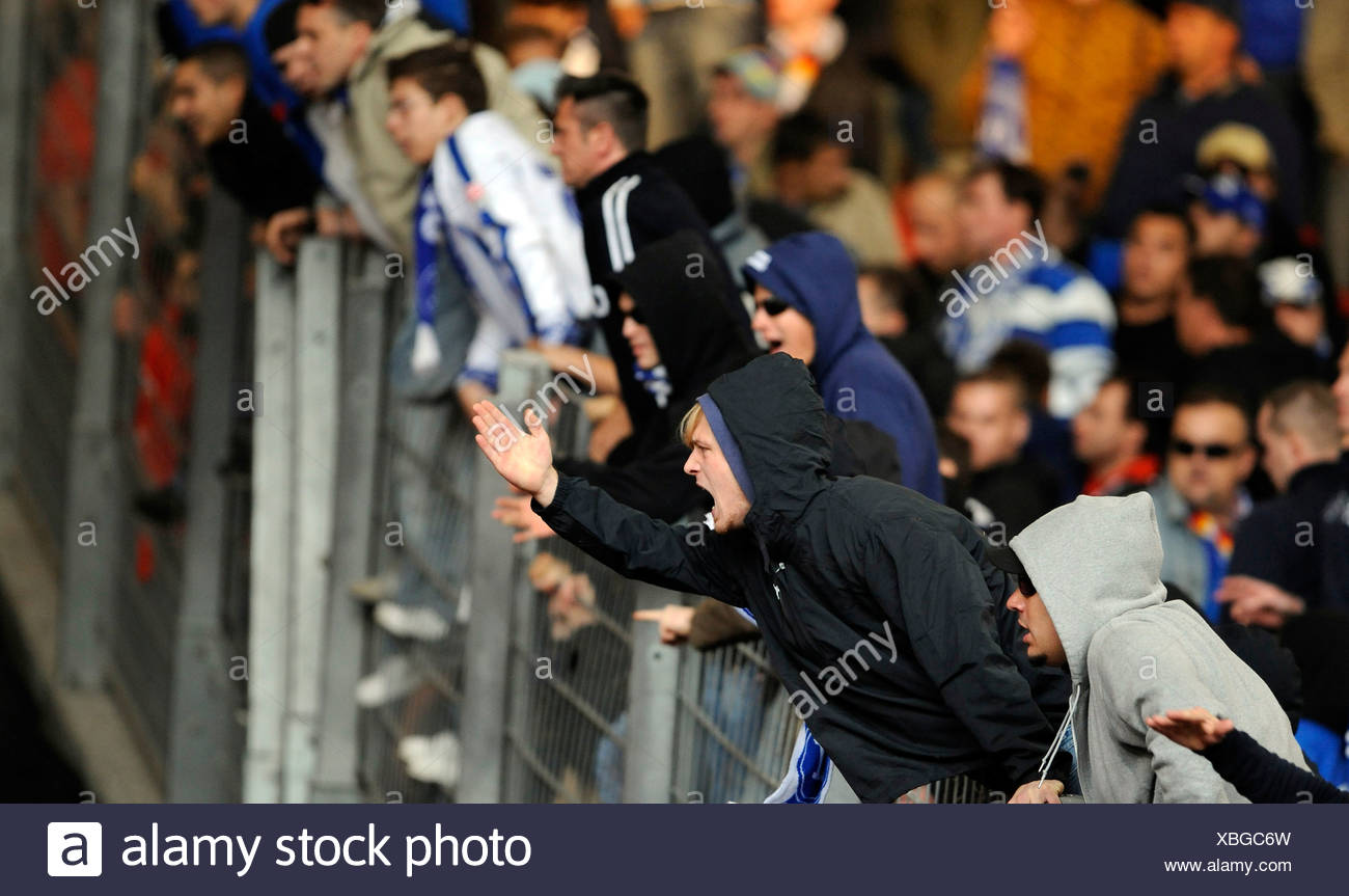 Aggressive hooligans climbing a separation fence - Stock Image