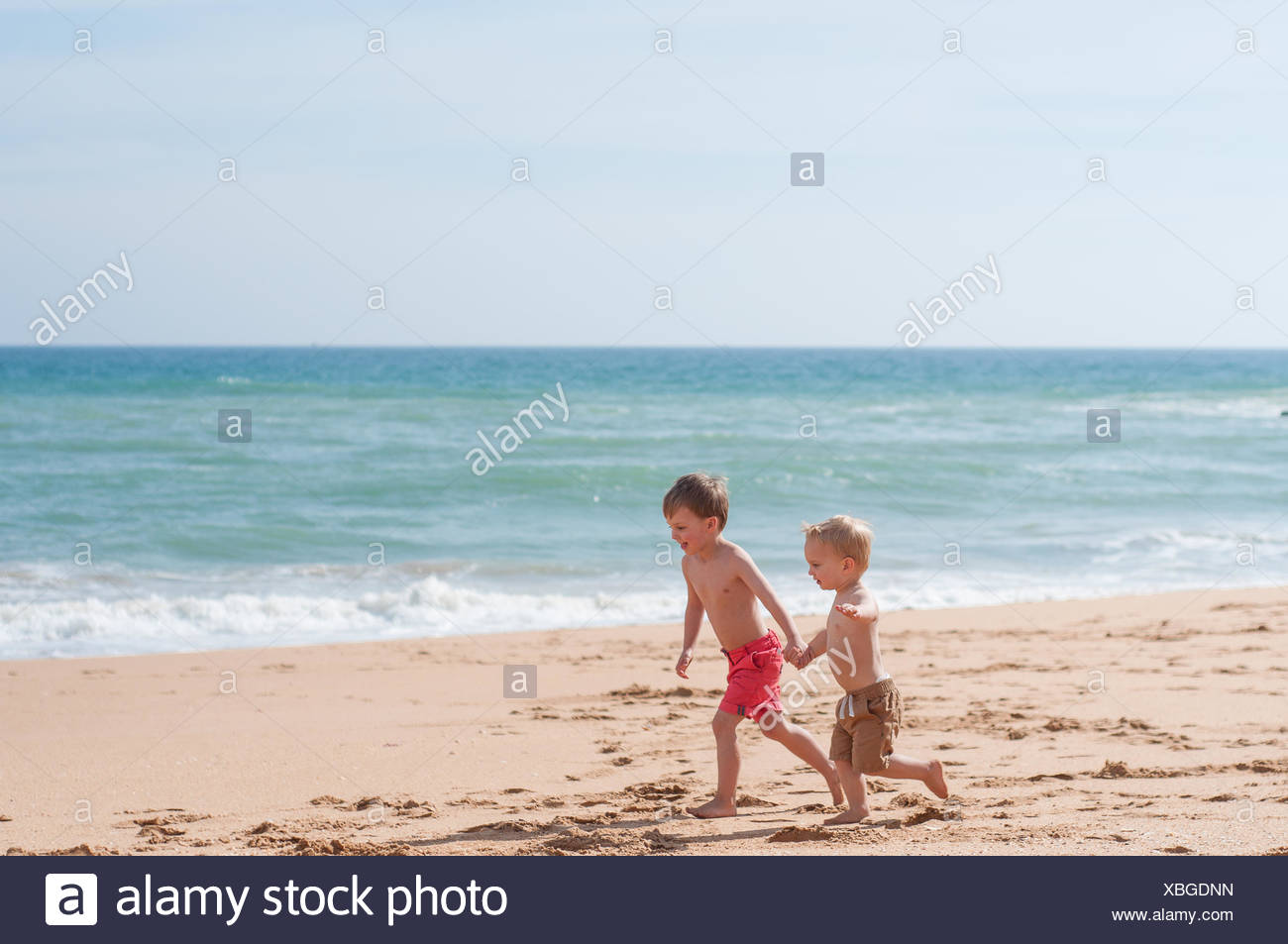 Two boys holding hands,  running on the beach - Stock Image