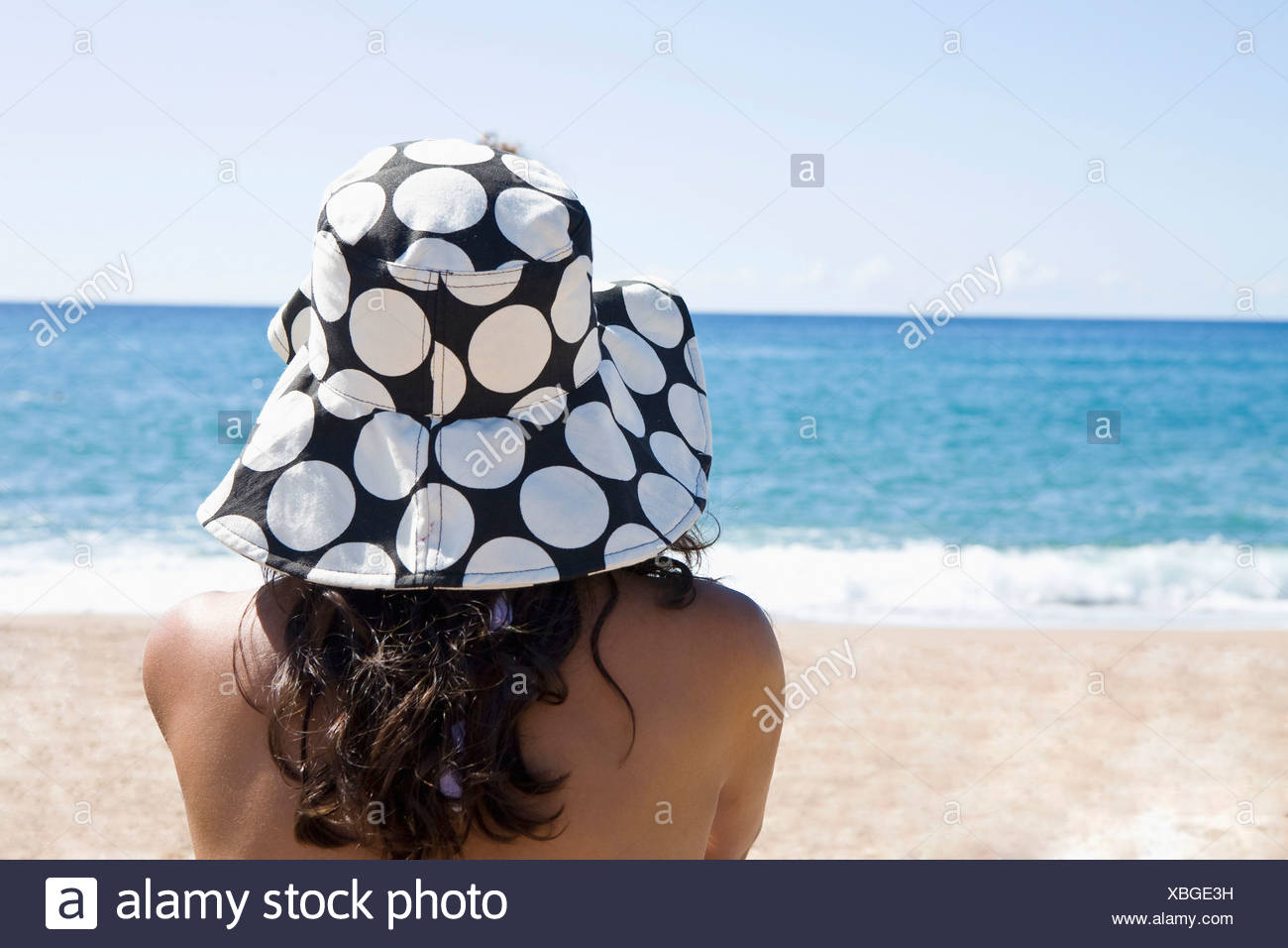 France, Corsica, Woman relaxing on beach, rear view - Stock Image